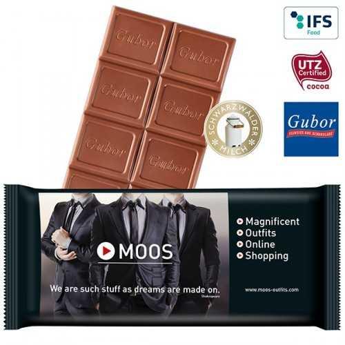 Tablette personnalisée de chocolat premium sous une feuille d'aluminium argentée, posée sur un insert en carton et le tout emb